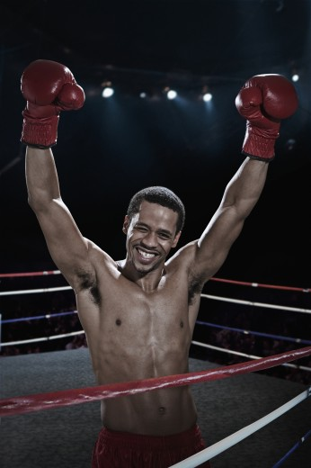 Smiling mixed race boxer with arms raised in boxing ring : Stock Photo