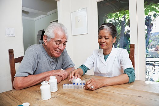 Home nurse filling daily vitamin container for elderly man : Stock Photo
