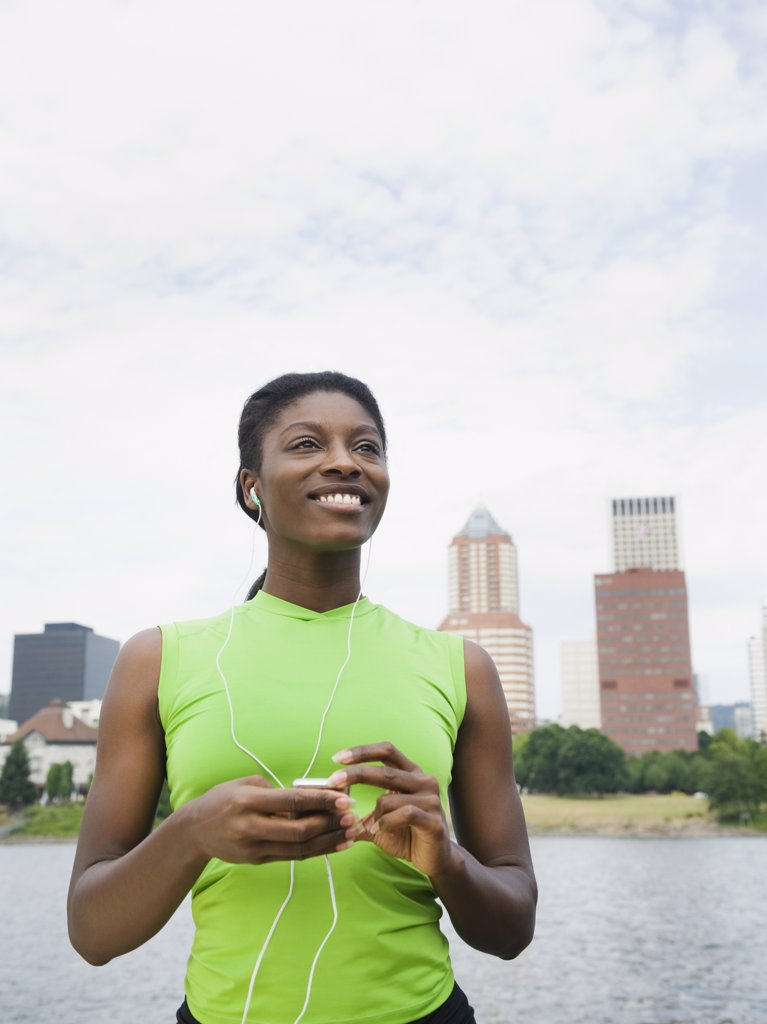 Stock Photo: 1589R-78826 African woman listening to headphones with city in background