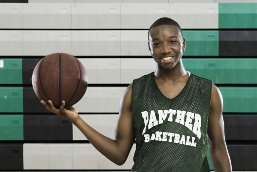 Stock Photo: 1589R-78857 African basketball player holding ball and smiling in gym