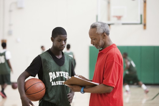 African coach and basketball player reviewing plays in gym : Stock Photo