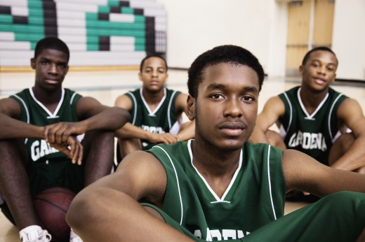 African basketball players sitting in gym : Stock Photo
