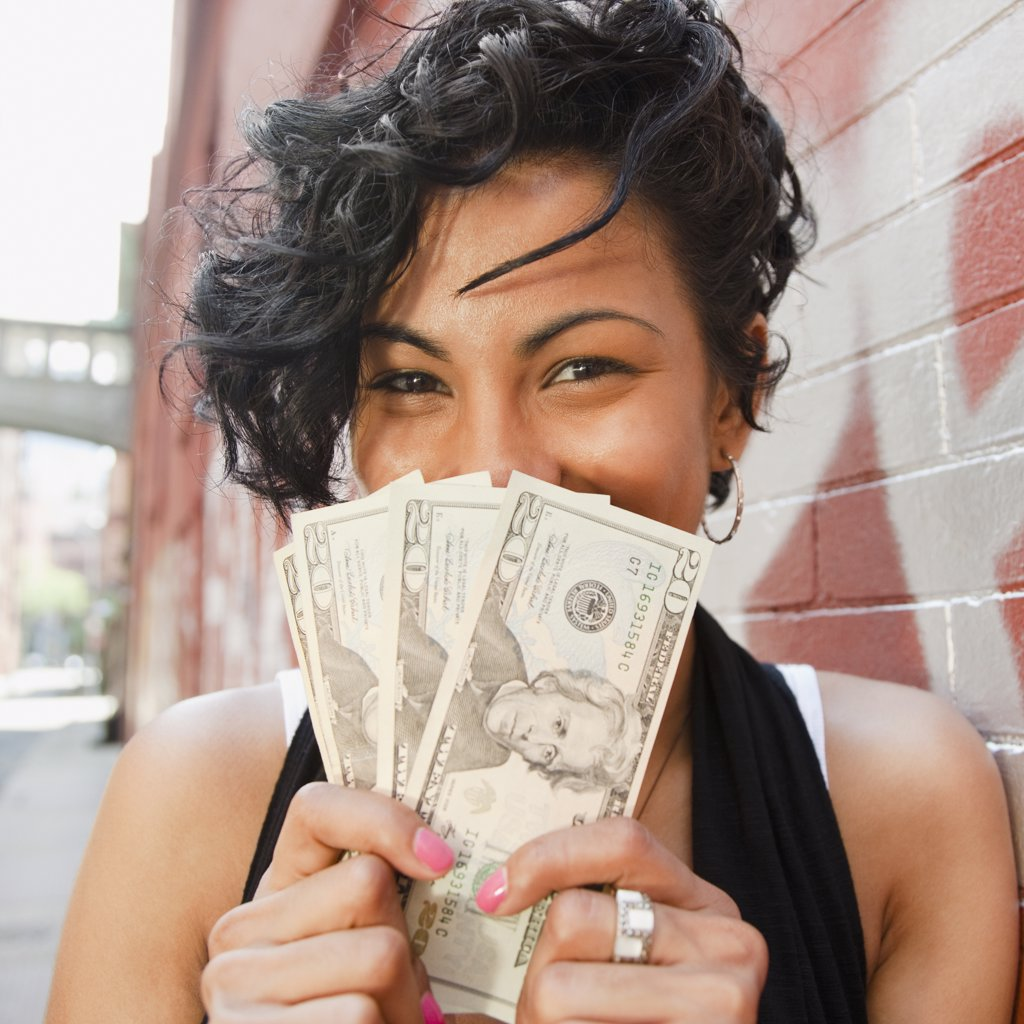 Mixed race woman holding twenty dollar bills : Stock Photo