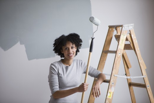 Stock Photo: 1589R-79082 Mixed race woman holding paint roller and leaning on ladder