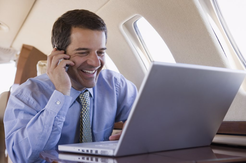 Hispanic businessman using laptop and cell phone on airplane : Stock Photo