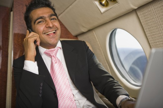 Stock Photo: 1589R-79326 Middle Eastern businessman using laptop and cell phone on private jet