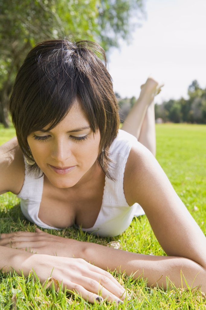 Hispanic woman laying in grass in park : Stock Photo