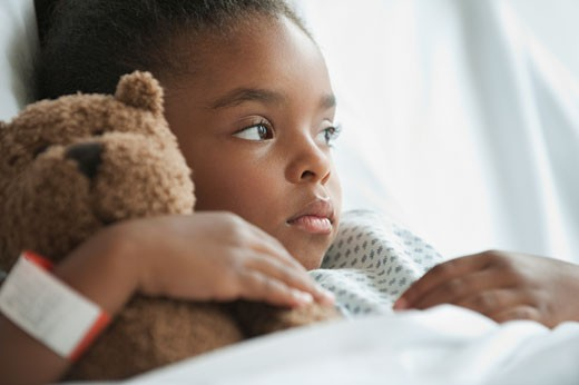 Stock Photo: 1589R-79672 Mixed race girl in hospital bed with teddy bear