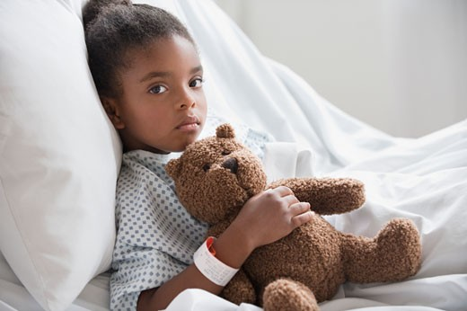 Mixed race girl in hospital bed with teddy bear : Stock Photo