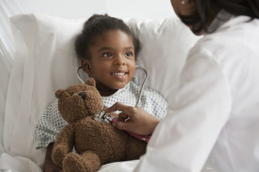 Stock Photo: 1589R-79677 Doctor examining girl in hospital bed