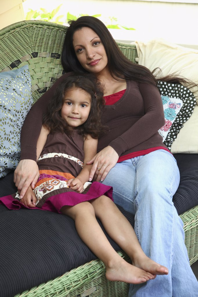 Mother sitting on sofa with daughter : Stock Photo