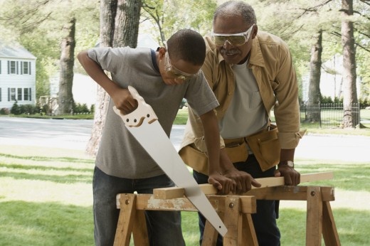 Stock Photo: 1589R-80272 African grandfather watching grandson saw wood