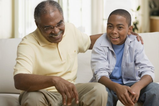 African grandfather and grandson sitting on sofa : Stock Photo