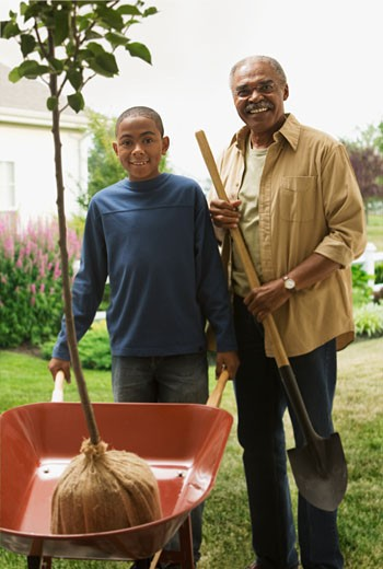 African grandfather and grandson planting tree : Stock Photo