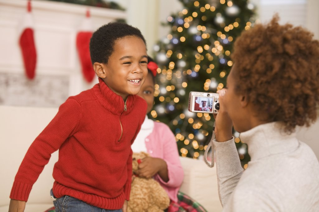 African mother taking picture of son at Christmas : Stock Photo