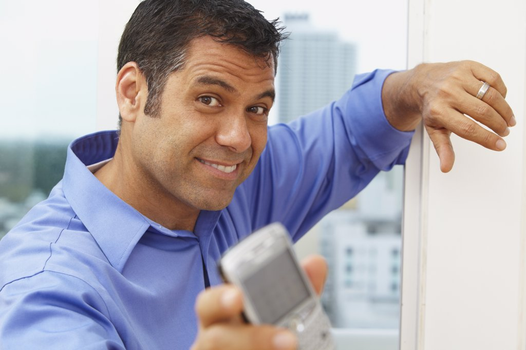Stock Photo: 1589R-80473 Hispanic businessman text messaging on cell phone