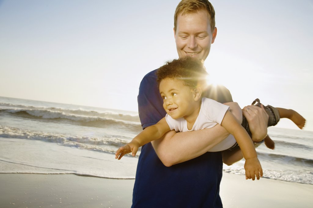 Father playing with mixed race son at beach : Stock Photo