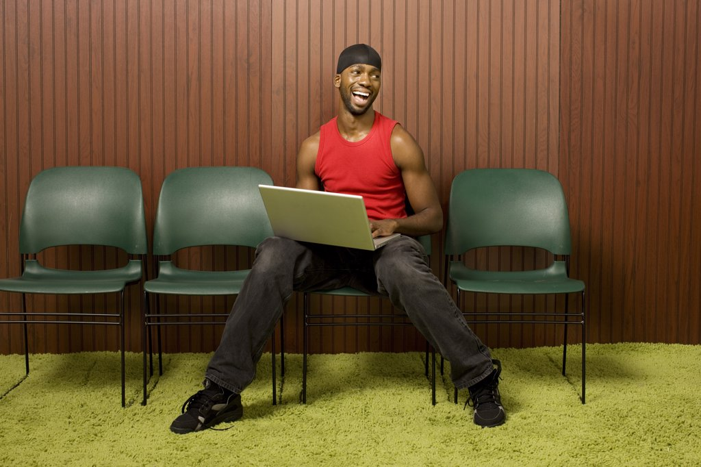 African man using laptop and laughing : Stock Photo