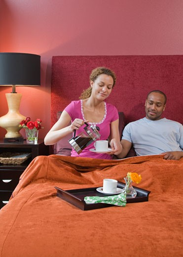 African couple drinking coffee in bed : Stock Photo