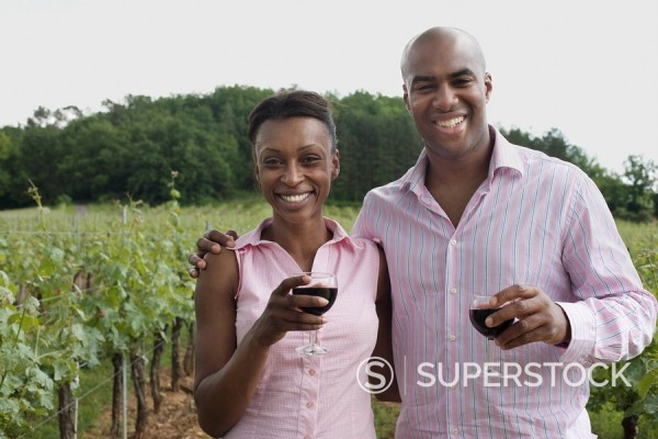 African couple holding wine glasses in vineyard : Stock Photo