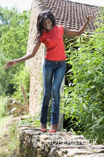 African woman balancing on stone wall : Stock Photo