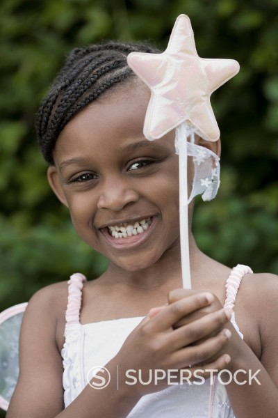 Close up of African girl in fairy costume with wand : Stock Photo