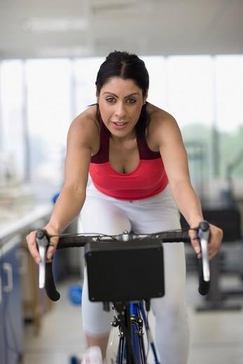 Hispanic woman riding stationary bicycle : Stock Photo