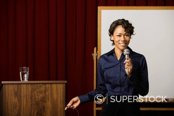 Mixed race businesswoman speaking on stage : Stock Photo