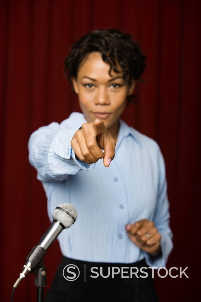 Stock Photo: 1589R-84619 Mixed race businesswoman speaking at microphone and pointing