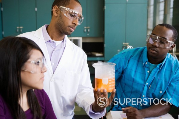 African teacher and students watching experiment in chemistry lab : Stock Photo
