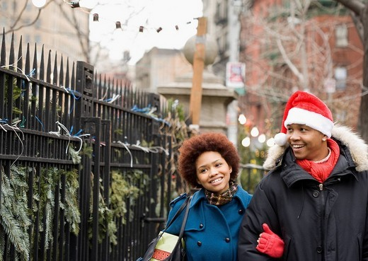 African man in santa hat walking outdoors with girlfriend : Stock Photo