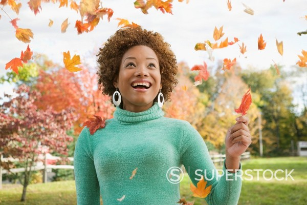 Hispanic woman watching falling autumn leaves : Stock Photo