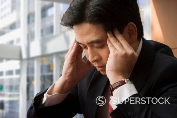 Chinese businessman rubbing forehead : Stock Photo