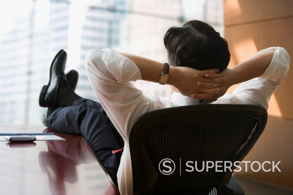 Chinese businessman with feet up on desk : Stock Photo