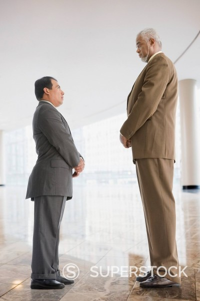 Stock Photo: 1589R-85523 Tall businessman looking down at short businessman