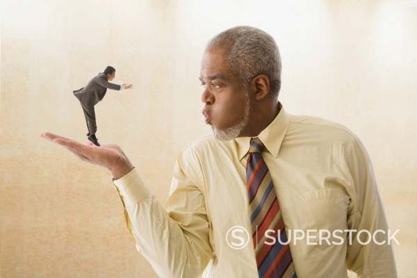 Giant businessman blowing on miniature businessman : Stock Photo