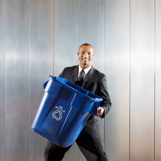 African businessman carrying recycling bin : Stock Photo