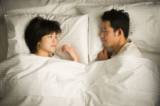 Korean couple laying face to face in bed : Stock Photo