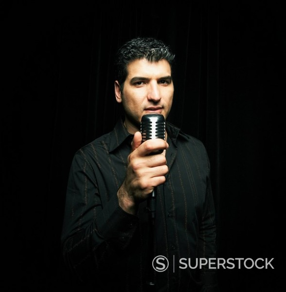 Stock Photo: 1589R-85993 Mixed race man standing at microphone