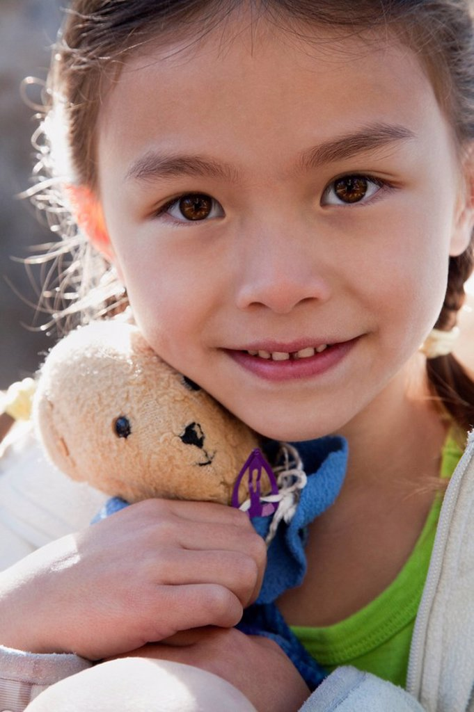 Stock Photo: 1589R-86053 Mixed race girl holding teddy bear