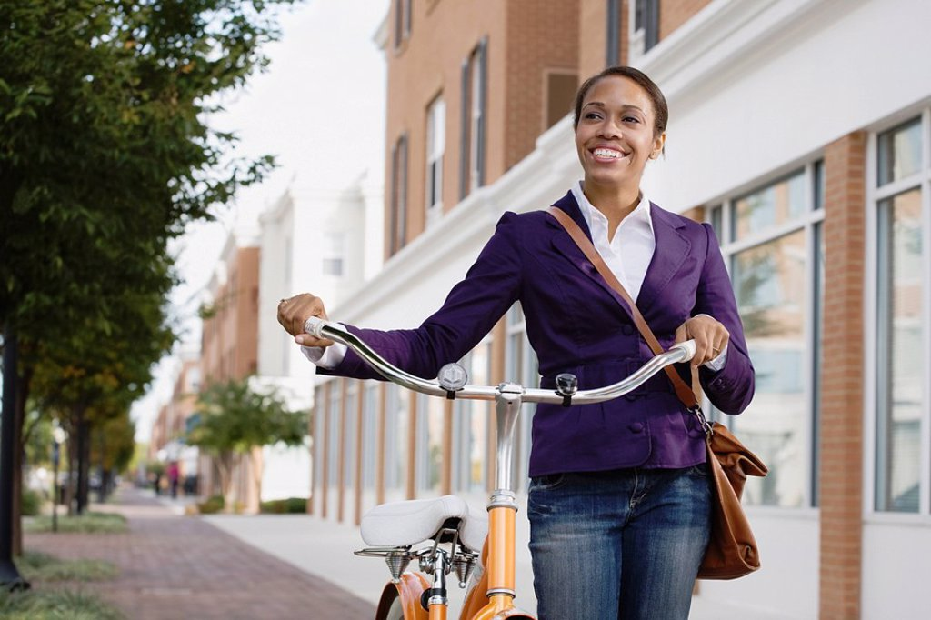 African American woman riding bicycle : Stock Photo