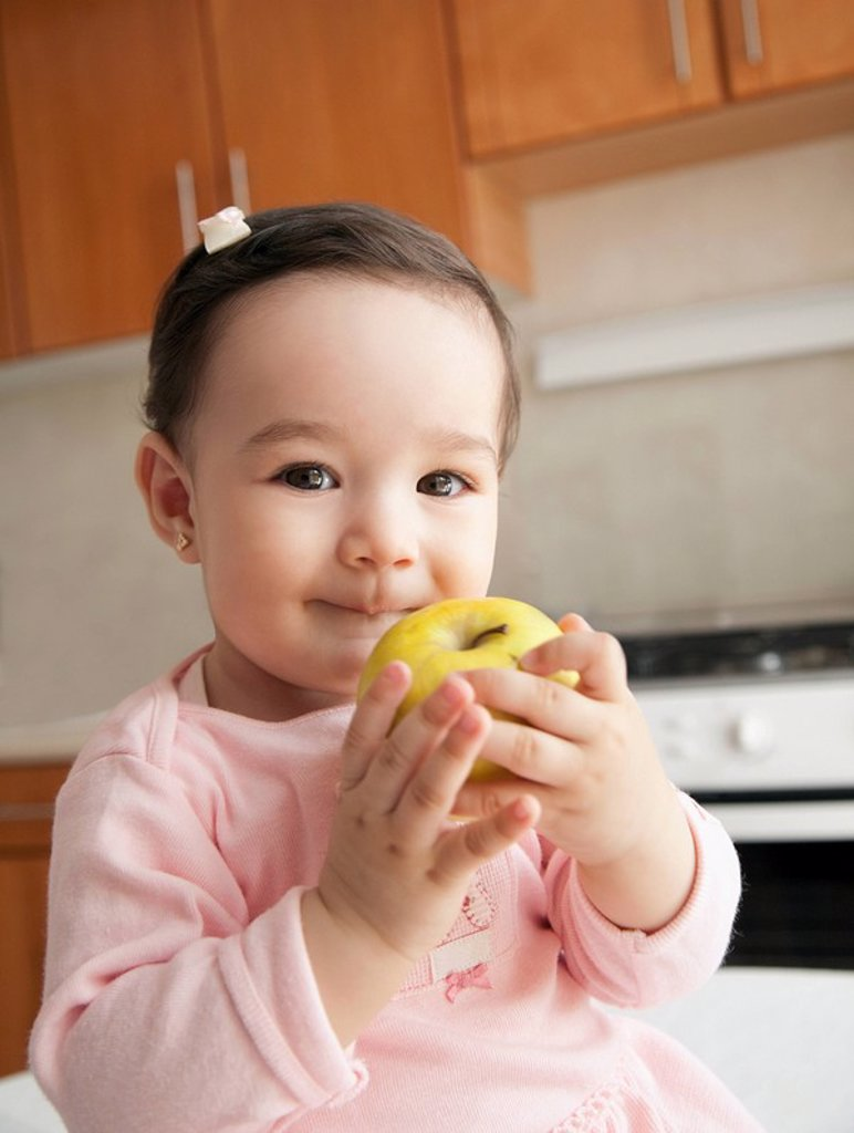 Stock Photo: 1589R-86818 Hispanic baby girl eating apple