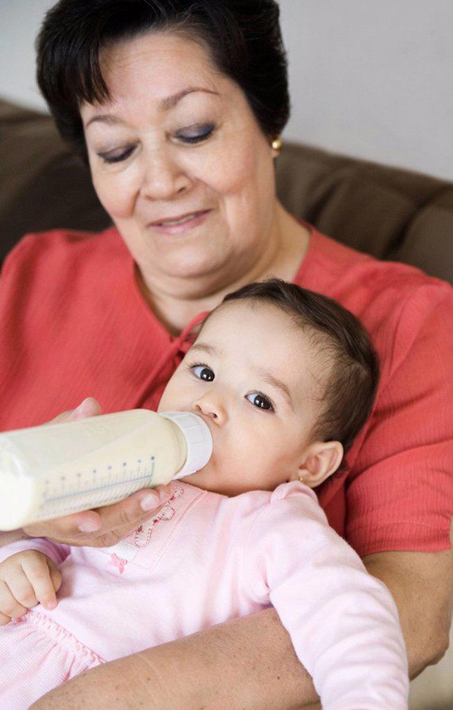 Stock Photo: 1589R-86820 Hispanic grandmother feeding baby