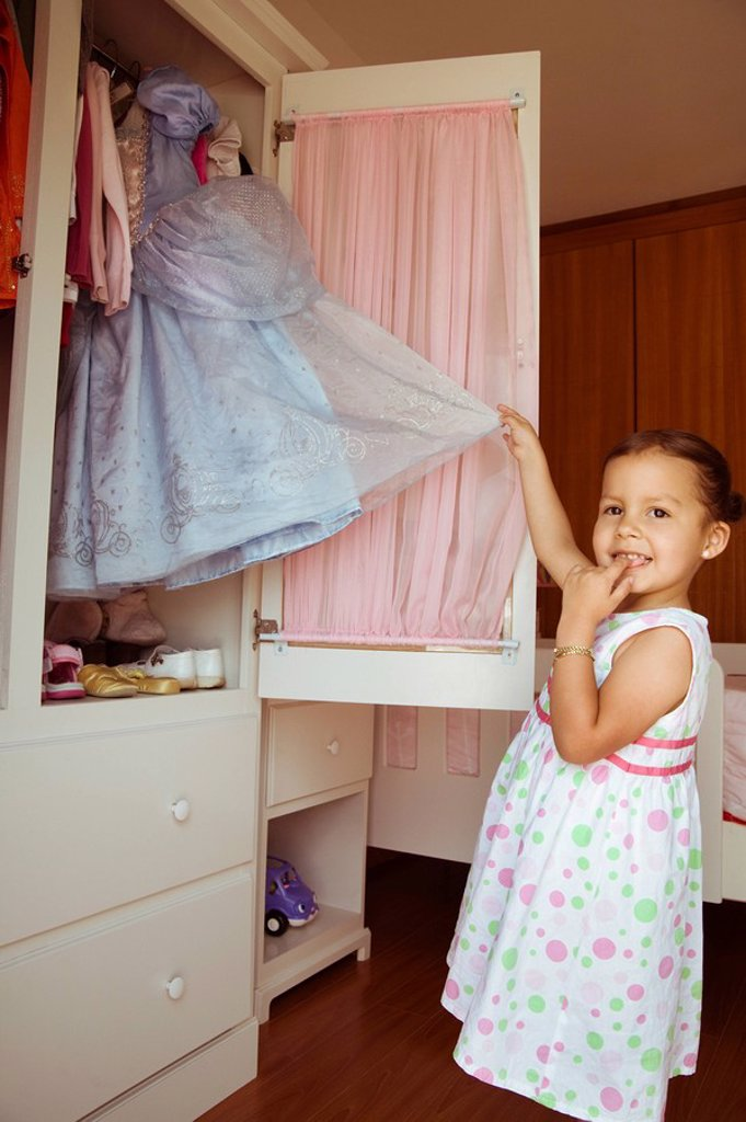 Stock Photo: 1589R-86826 Hispanic girl taking costume from closet