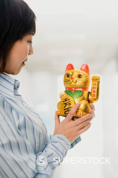 Stock Photo: 1589R-86969 Chinese woman looking at beckoning cat