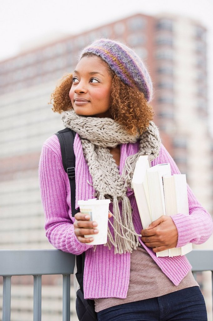 Mixed race woman holding books and drinking coffee : Stock Photo