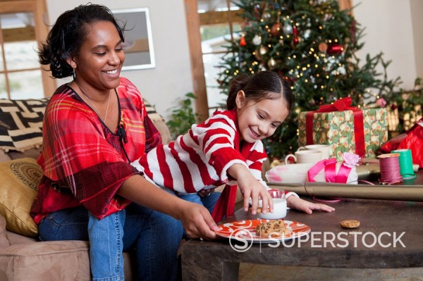 Mixed race mother and daughter eating cookies by Christmas tree : Stock Photo
