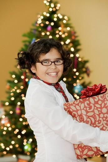 Mixed race girl holding Christmas gift : Stock Photo