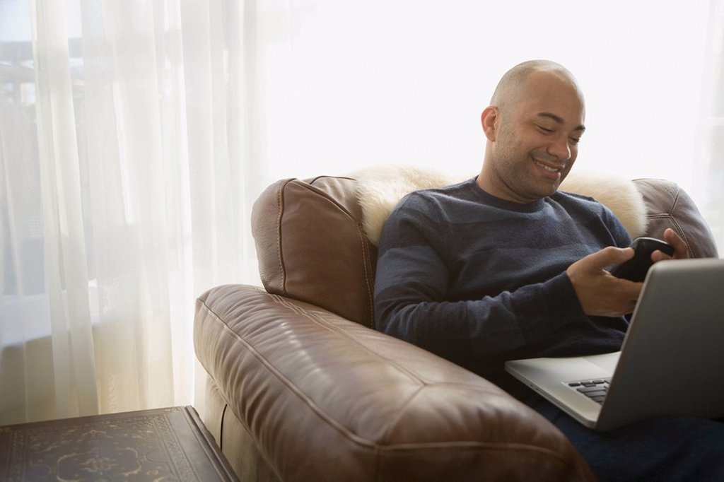 Mixed race man with laptop using cell phone : Stock Photo