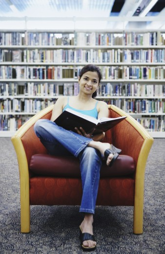 Woman holding book in library : Stock Photo
